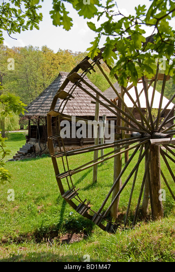 Romania's Museum of Traditional Folk Civilization water wheel and dwellings at Sibiu in Transylvania - Stock Image
