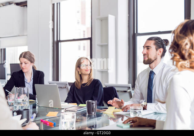 Businessman discussing with colleagues at conference table during meeting - Stock-Bilder
