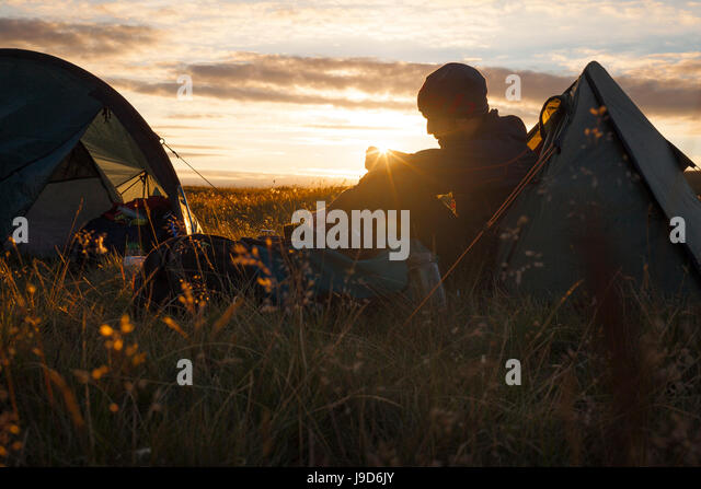 A camper sits in the evening sun, Picws Du, Black Mountain, Brecon Beacons National Park, Wales, United Kingdom, - Stock-Bilder