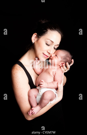 The beauty of motherhood, mother and cute baby. Parent holding infant with care and love, on black. - Stock Image