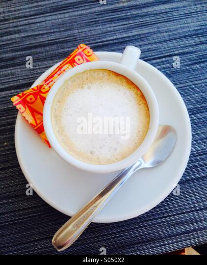 Coffee Cup and sugar packet.white coffee in white cup with spoon on white saucer and orange sugar packet. - Stock Image