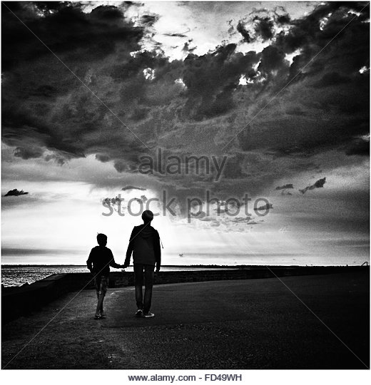 Rear View Of Father And Son Holding Hands While Walking On Beach Against Cloudy Sky - Stock-Bilder