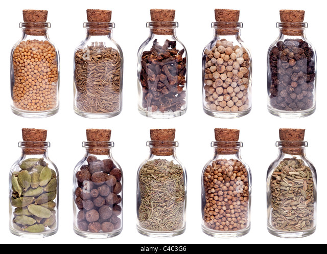 Assortment of different spices in glass bottles isolated on white - Stock Image