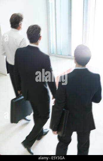 Business associates chatting while leaving office building together - Stock-Bilder