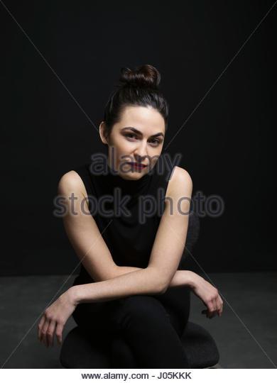 Portrait confident, serious brunette woman against black background - Stock Image