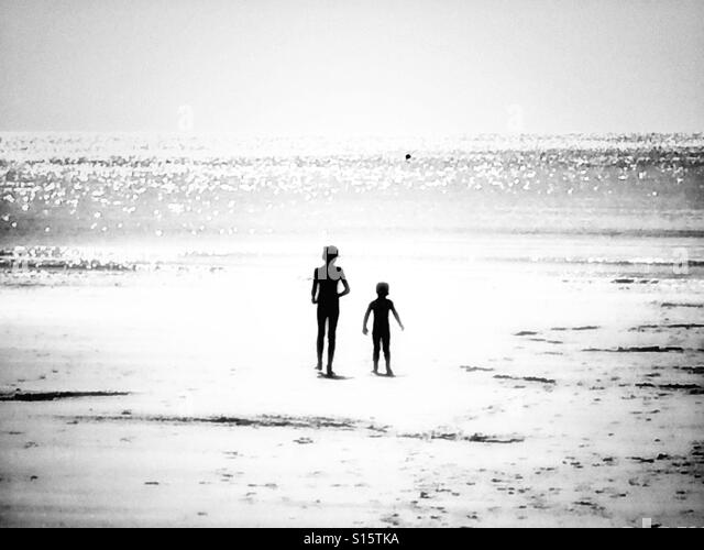 2 children walking towards the shallow sea on a deserted beach - Stock-Bilder
