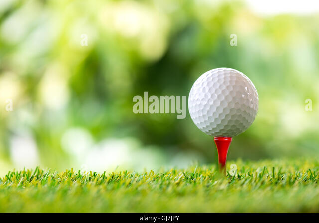 golf ball on tee in golf course - Stock Image