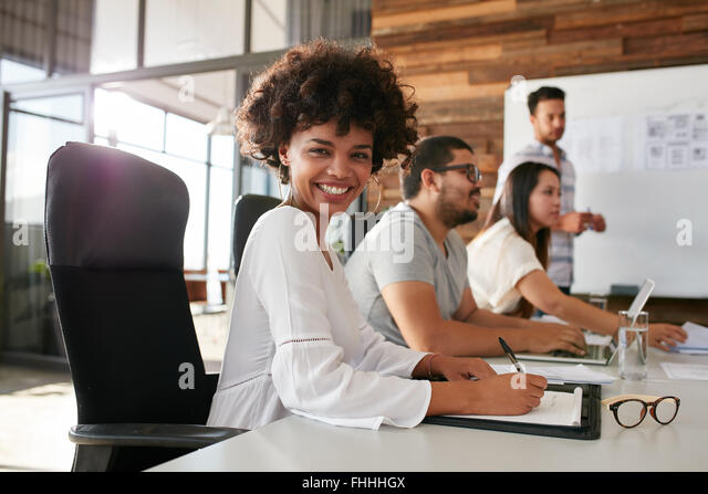 Portrait of happy young african woman sitting at a business presentation with colleagues in boardroom. Female designer - Stock Image