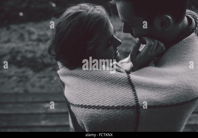 Young couple wrapped in plaid - Stock-Bilder