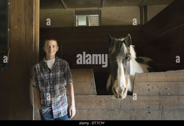 A man standing by horsebox in the stables at an animal sanctuary A horse with its head over the gate Saugerties - Stock Image