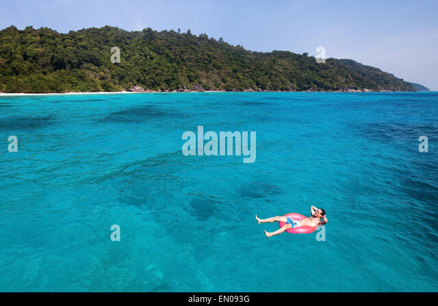 travel insurance concept, man swimming in lifebuoy on paradise beach - Stock-Bilder
