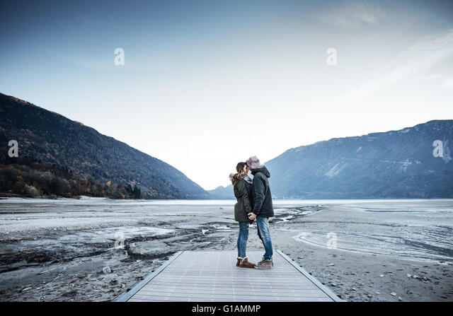 Romantic young couple on a pier holding hands, lake and mountains on background - Stock Image