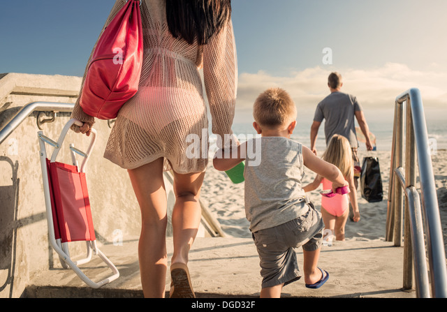 Young woman arriving at beach with son - Stock Image