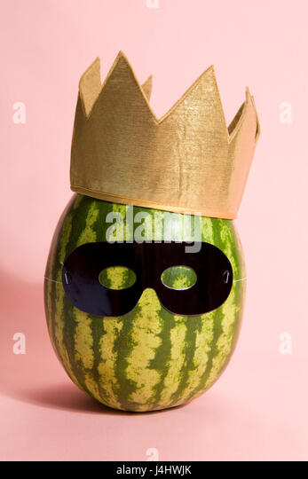 Superwatermelon wearing a black mask on a pink background - Stock Image