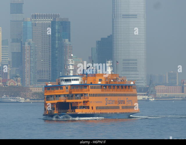 Staten Island Ferry leans to right as tourist crowd the starboard side to photograph Statue of Liberty - Stock Image