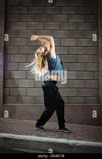 Teenage girl dancing hip-hop over the street wall - Stock Image