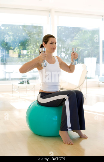 Weightlifting. Woman lifting dumbbells whilst sitting on an exercise ball. - Stock Image
