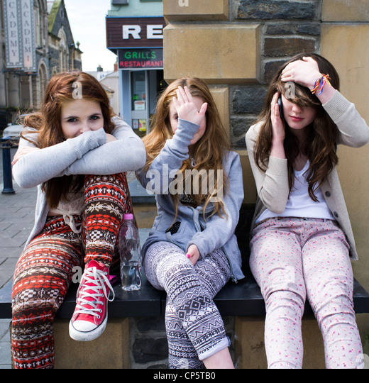 Three teenage girls sitting together outside outdoors, , three wise monkeys - not speaking, not seeing, not hearing - Stock-Bilder