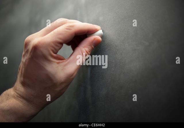 A man male teacher left hand writes using chalk on a chalkboard blackboard. - Stock Image