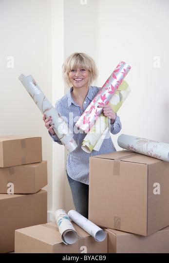 Woman holding wallpaper samples - Stock Image