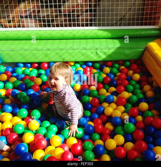 Laughing Baby In Pool Of Multi Colored Balls - Stock Image