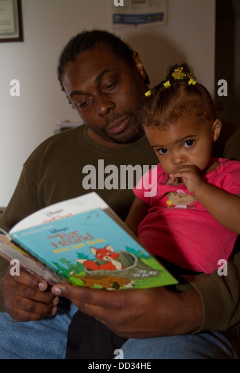 African-American male former inmate reading to his young daughter. This inmate managed to get a degree after his - Stock Image