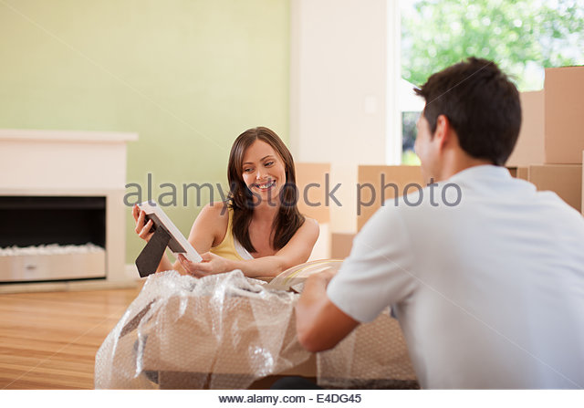 Couple unpacking pictures in new house - Stock-Bilder