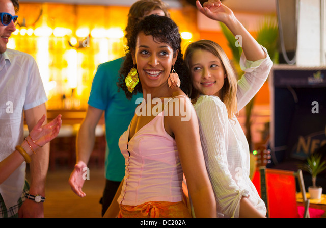 Two females dancing back to back in bar - Stock Image