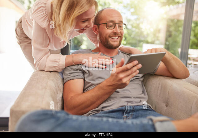 Happy woman standing behind her husband sitting of sofa in living room, both looking at a digital tablet smiling. - Stock Image