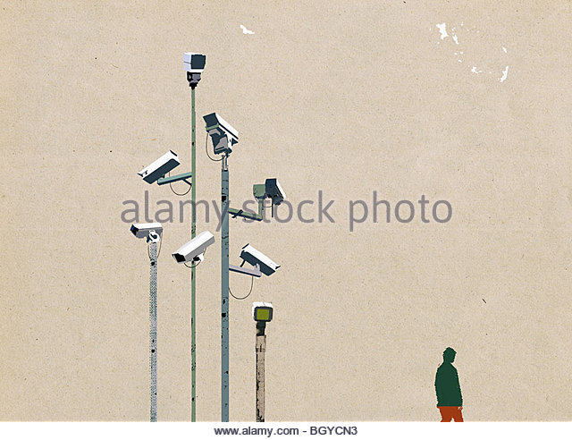 Man waking beneath surveillance cameras - Stock Image