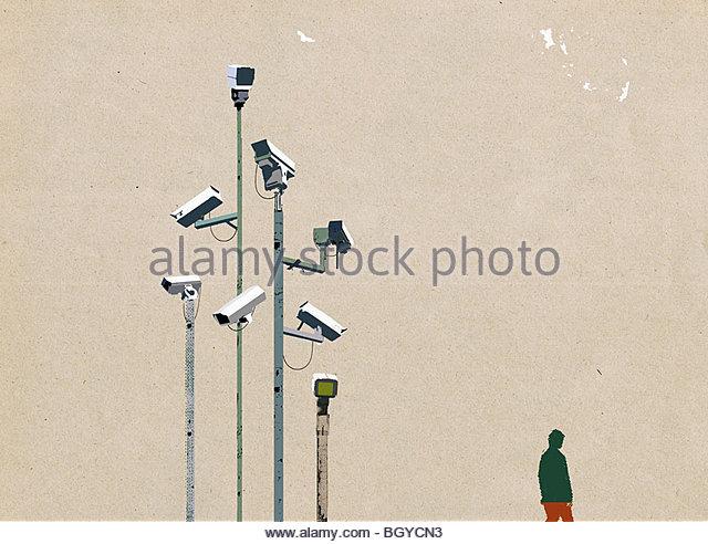 Man waking beneath surveillance cameras - Stock Image