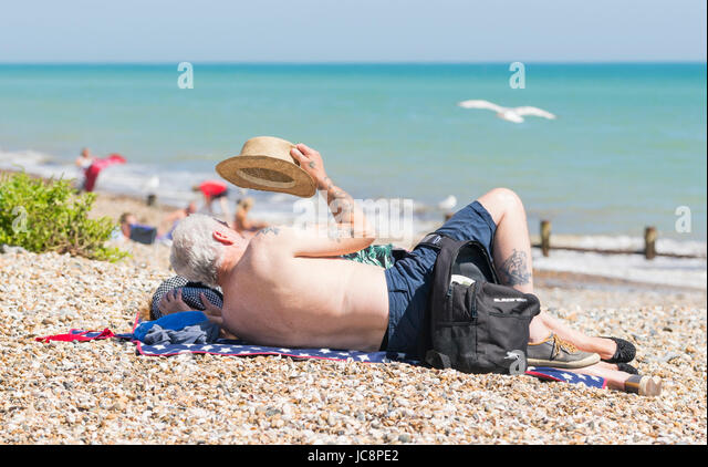 Elderly couple relaxing on a shingle beach on a hot Summer's day in June 2017 in Littlehampton, West Sussex, - Stock Image