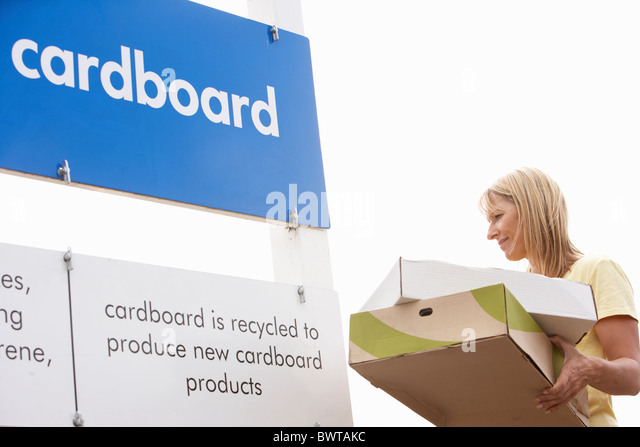 Woman At Recycling Centre Disposing Of Cardboard - Stock Image