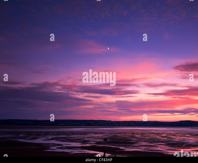 A crescent moon over the Dee Estuary looking towards north Wales from the Wirral peninsula. - Stock Image