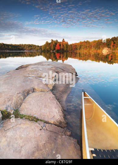 Canoe at a rocky shore of lake George. Beautiful sunset fall nature scenery. Killarney Provincial Park, Ontario, - Stock Image