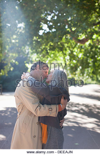 Couple hugging on sunny road under trees - Stock Image