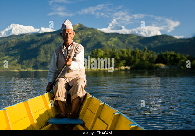 Nepalese man rowing traditional boat - Stock Image