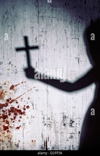 shadow of a person with a crucifix on a bloody white wall - Stock Image