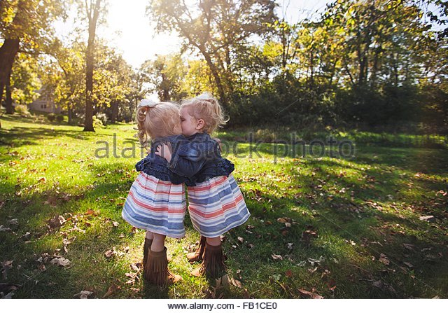 Twin girls wearing matching dresses face to face hugging and kissing - Stock Image