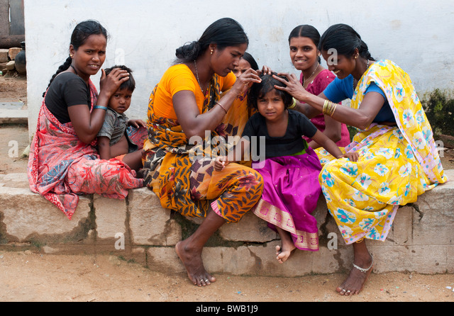 Indian mothers nitpicking young girls head in a rural indian village community - Stock Image