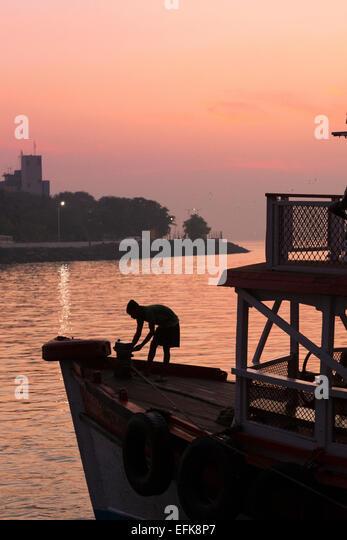 India, Maharashtra, Mumbai, Colaba district,  man silhouetted on boat in Mumbai harbour near Gateway of India - Stock Image