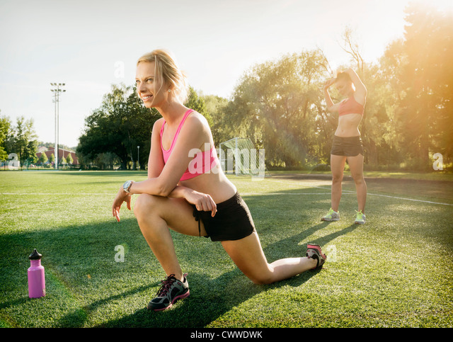 Runners stretching on grass in park - Stock Image