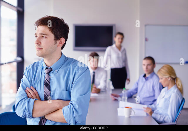 business man  on a meeting in offce with colleagues in background - Stock Image