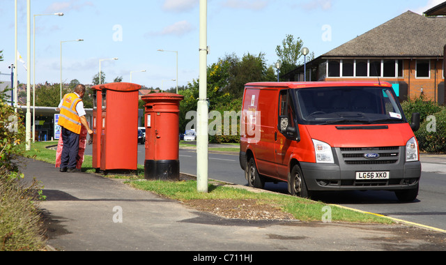 A postman collecting mail from a post box - Stock Image