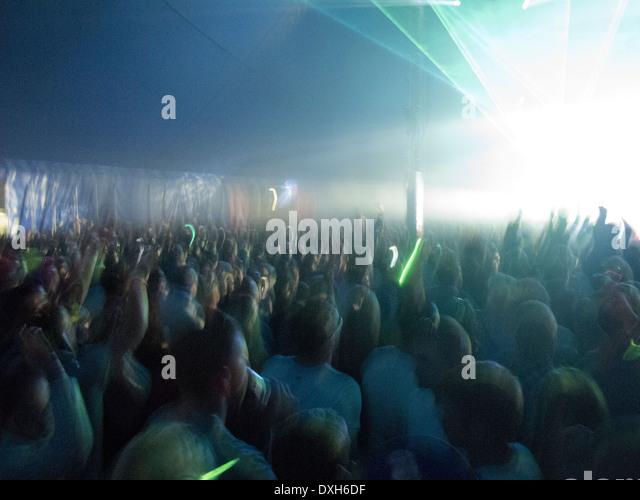Crowd facing illuminated stage - Stock Image