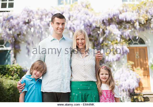 Family standing together outside house - Stock Image
