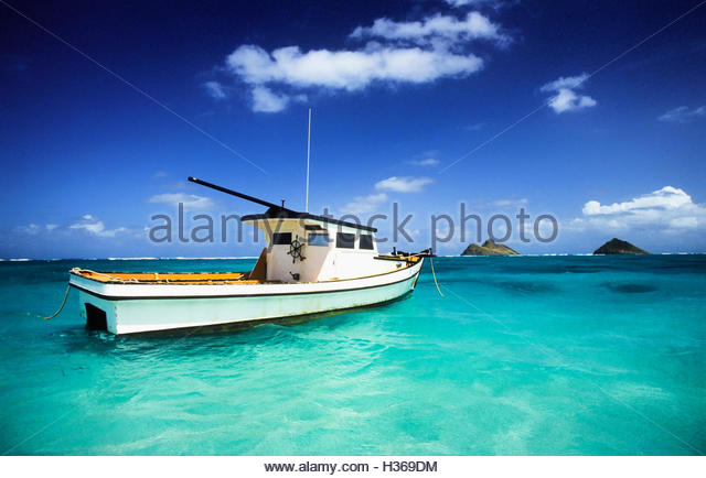 Hawaiian fishing boat anchored off sand beach with Mokolua islands in background - Stock Image