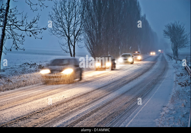 Cars at dusk on a snowy country road near Bad Homburg in the Taunus. - Stock-Bilder