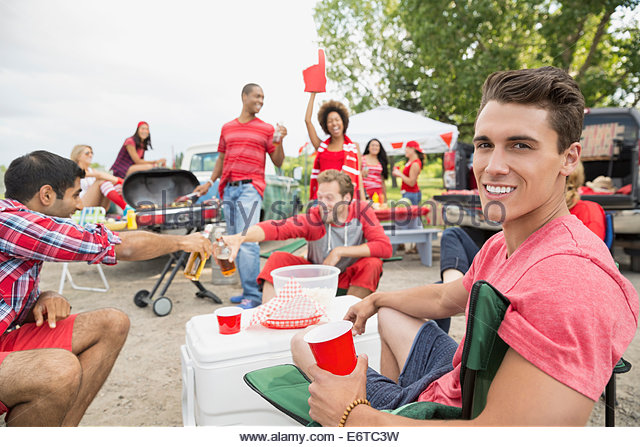 Man relaxing at tailgate barbecue in field - Stock Image
