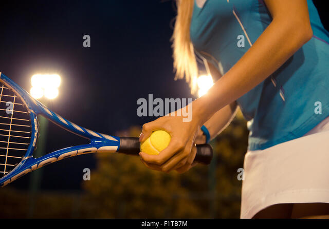 Closeup portrait of a female tennis player holding racket and ball - Stock-Bilder
